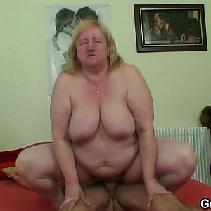 Grandma with huge melons likes riding his young cock
